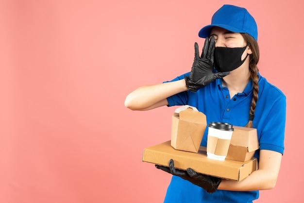 Halbkörperaufnahme eines kuriermädchens mit medizinischer maske und handschuhen, das befehle hält, die andere auf pastellfarbenem pfirsichhintergrund anrufen
