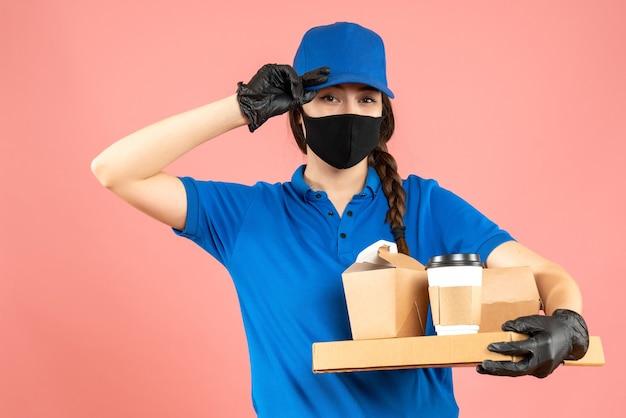 Halbkörperaufnahme eines kuriermädchens mit medizinischer maske und handschuhen, das bestellungen auf pastellfarbenem pfirsichhintergrund hält holding