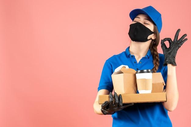 Halbkörperaufnahme eines kuriermädchens mit medizinischer maske und handschuhen, das bestellungen hält, die eine brillengeste auf pastellfarbenem pfirsichhintergrund machen