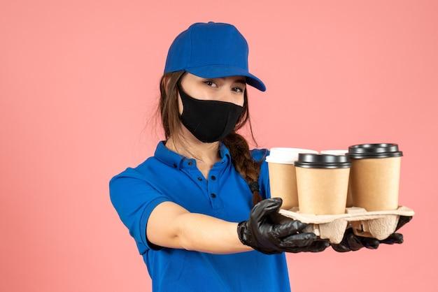 Halbkörperaufnahme eines kuriermädchens mit medizinischer maske und handschuhen, die kaffee auf pastellfarbenem pfirsichhintergrund halten holding