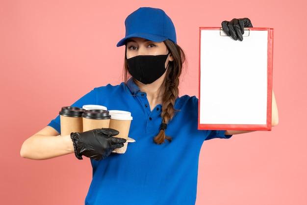 Halbkörperaufnahme eines kuriermädchens mit schwarzen medizinischen maskenhandschuhen, die dokumente und kaffee auf pastellfarbenem pfirsichhintergrund halten holding