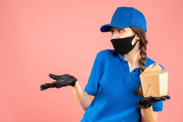 Halbkörperaufnahme eines neugierigen kuriermädchens mit medizinischer maske und handschuhen, das eine kleine schachtel auf pastellfarbenem pfirsichhintergrund hält holding