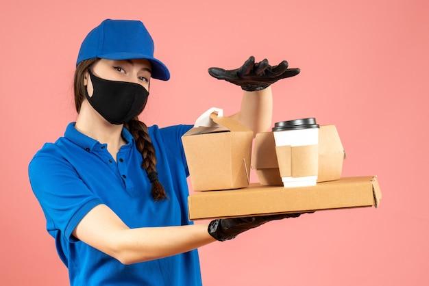 Halbkörperaufnahme eines selbstbewussten kuriermädchens mit medizinischer maske und handschuhen, das bestellungen auf pastellfarbenem pfirsichhintergrund hält holding