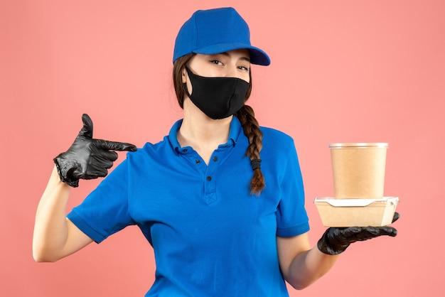 Halbkörperaufnahme eines selbstbewussten kuriermädchens mit medizinischer maske und handschuhen, das eine kleine kaffeebox auf pastellfarbenem pfirsichhintergrund hält holding