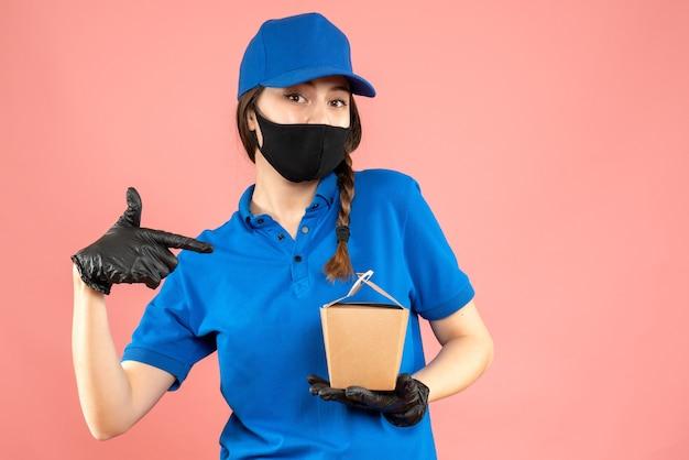 Halbkörperaufnahme eines selbstbewussten kuriermädchens mit medizinischer maske und handschuhen, das eine kleine schachtel auf pastellfarbenem pfirsichhintergrund hält holding