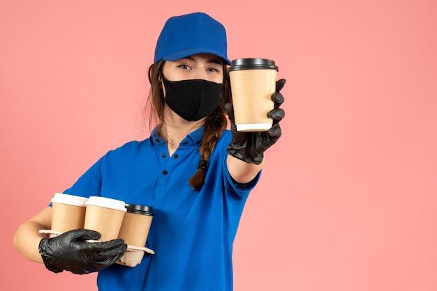Halbkörperaufnahme eines selbstbewussten kuriermädchens mit schwarzen medizinischen maskenhandschuhen, die kaffee auf pastellfarbenem pfirsichhintergrund halten holding