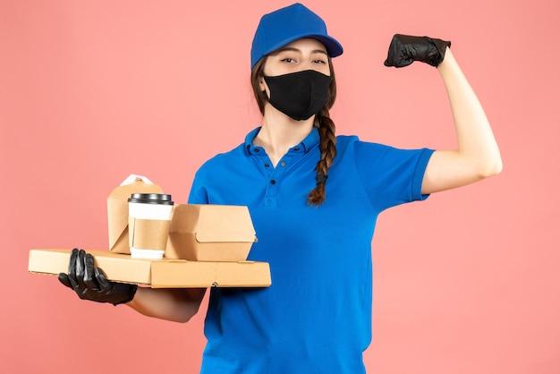 Halbkörperaufnahme eines stolzen kuriermädchens mit medizinischer maske und handschuhen, das bestellungen auf pastellfarbenem pfirsichhintergrund hält holding