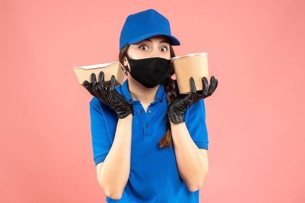 Halbkörperaufnahme eines überraschten kuriermädchens mit medizinischer maske und handschuhen, das eine kleine kaffeebox auf pastellfarbenem pfirsichhintergrund hält