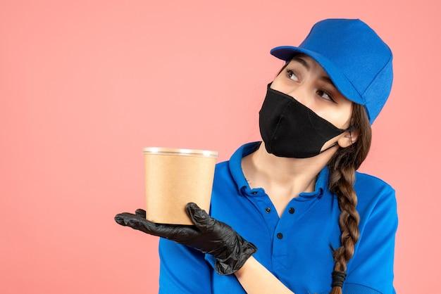 Halbkörperaufnahme eines verträumten kuriermädchens mit medizinischer maske und handschuhen, die kaffee auf pastellfarbenem pfirsichhintergrund halten