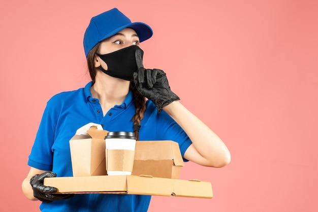 Halbkörperaufnahme eines verwirrten kuriermädchens mit medizinischer maske und handschuhen, das bestellungen auf pastellfarbenem pfirsichhintergrund hält holding