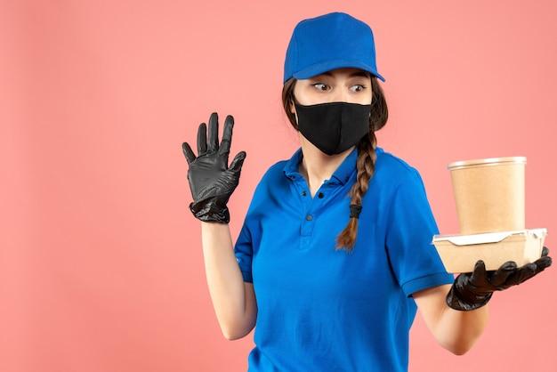 Halbkörperaufnahme eines wundernden kuriermädchens mit medizinischer maske und handschuhen, das eine kleine kaffeebox auf pastellfarbenem pfirsichhintergrund hält
