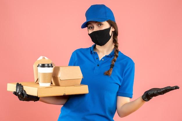 Halbkörperaufnahme eines zufriedenen kuriermädchens mit medizinischer maske und handschuhen, das bestellungen auf pastellfarbenem pfirsichhintergrund hält holding