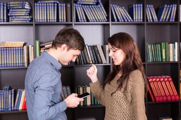 Halbkörperaufnahme junger liebhaber in trendigen outfits, die zusammen auf das handy schauen, während sie in der nähe der bücherregale stehen.