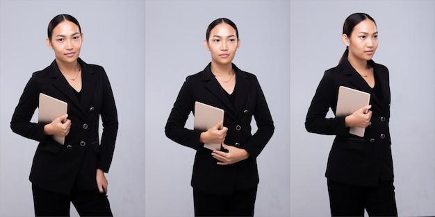Halbkörperporträt der 20er jahre asiatische frau schwarzes haar formale anzugjacke. bürofrau trägt ein digitales tablet-lächeln über grauem hintergrund isoliert