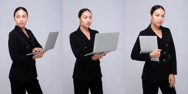 Halbkörperporträt der 20er jahre asiatische frau schwarzes haar formale anzugjacke. bürofrau trägt notebook-laptop-lächeln über grauem hintergrund isoliert