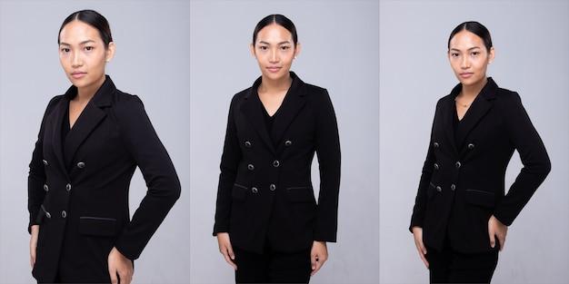 Halbkörperporträt der 20er jahre asiatische frau schwarzes haar formale anzugjacke. bürofrau wirft viele blicke auf und lächelt über grauem hintergrund isoliert
