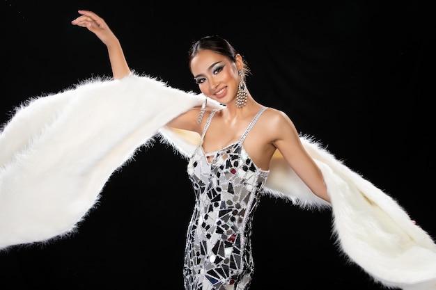 Halbkörperporträt der asiatischen transgender-frau im kabarett-karneval phantasie-spiegel reflektieren silbernen kleidkleid-kopf, der über dunklem hintergrund gesetzt wird