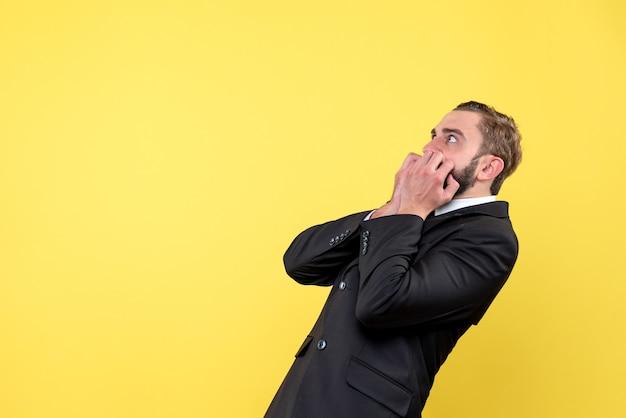 Halbkörperporträt des verblüfften jungen mannes, der sich auf etwas in der linken seite konzentriert