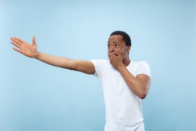 Halblanges nahaufnahmeporträt des jungen afroamerikanermannes im weißen hemd auf blauem hintergrund. menschliche emotionen, gesichtsausdruck, anzeige, verkaufskonzept. zeigen, wählen, erstaunt. copyspace.
