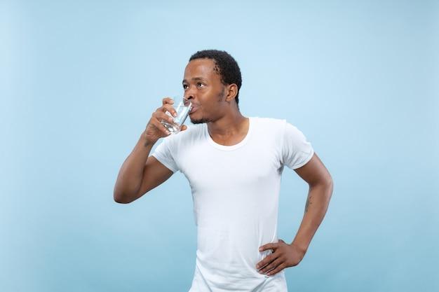 Halblanges nahaufnahmeporträt des jungen afroamerikanermannes im weißen hemd auf blauem hintergrund. menschliche emotionen, gesichtsausdruck, anzeigenkonzept. ein glas halten und wasser trinken.