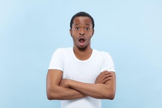 Halblanges nahaufnahmeporträt des jungen afroamerikanermannes im weißen hemd auf blauem hintergrund. menschliche emotionen, gesichtsausdruck, werbung, verkauf, konzept. stehende hände gekreuzt, geschockt und erstaunt.