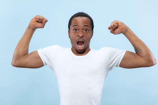 Halblanges nahaufnahmeporträt des jungen afroamerikaners im weißen hemd auf blauem raum. menschliche gefühle, gesichtsausdruck, anzeige, konzept