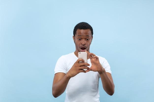 Halblanges nahaufnahmeporträt des jungen afroamerikaners im weißen hemd auf blauer wand. menschliche emotionen, gesichtsausdruck, anzeigenkonzept. ein foto oder einen vlog-inhalt auf seinem smartphone aufnehmen.