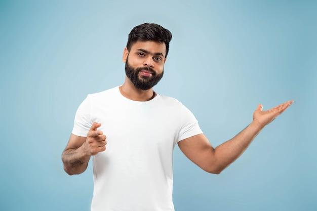 Halblanges nahaufnahmeporträt des jungen hindu-mannes im weißen hemd auf blau.