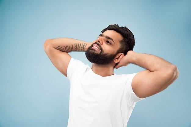 Halblanges nahaufnahmeporträt des jungen hindu-mannes im weißen hemd auf blauem hintergrund. menschliche emotionen, gesichtsausdruck, anzeigenkonzept. negativer raum. ausruhen, entspannen, ruhig aussehen.