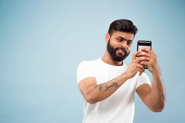 Halblanges nahaufnahmeporträt des jungen hindu-mannes im weißen hemd auf blauem hintergrund. menschliche emotionen, gesichtsausdruck, anzeigenkonzept. negativer raum. selfie oder videoblog, vlog, chating machen.