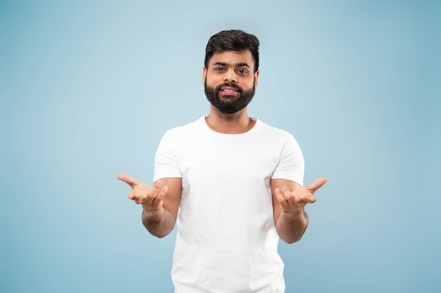 Halblanges nahaufnahmeporträt des jungen hindu-mannes im weißen hemd auf blauem raum