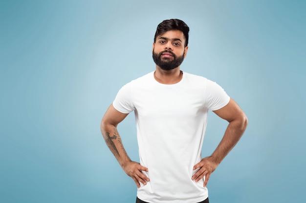 Halblanges nahaufnahmeporträt des jungen hindu-mannes im weißen hemd auf blauer wand. menschliche emotionen, gesichtsausdruck, anzeigenkonzept. negativer raum. posieren, stehen und lächeln sieht ruhig aus.