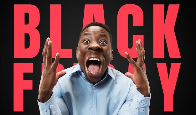 Halblanges nahaufnahmeporträt des jungen mannes auf schwarzem hintergrund mit schwarzem freitag-schriftzug