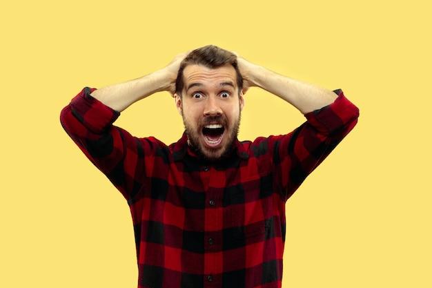 Halblanges nahaufnahmeporträt des jungen mannes im hemd auf gelbem raum. die menschlichen emotionen, gesichtsausdruck konzept. trendige farben