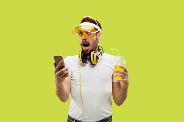 Halblanges nahaufnahmeporträt des jungen mannes im hemd auf gelbem raum. männliches model mit kopfhörern und getränk.