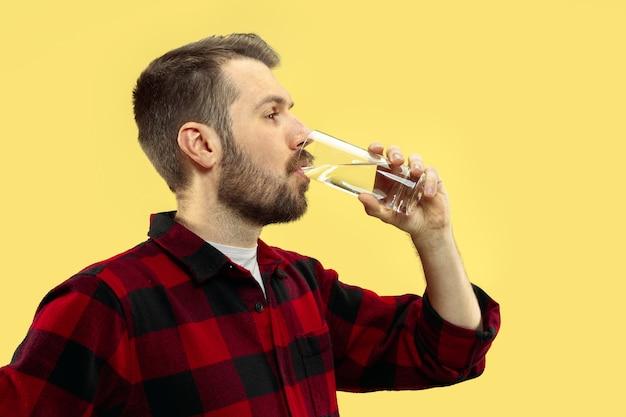 Halblanges nahaufnahmeporträt des jungen mannes im hemd auf gelbem raum