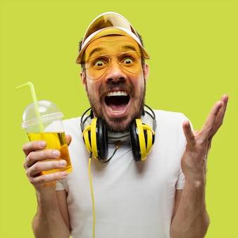 Halblanges nahaufnahmeporträt des jungen mannes im hemd. männliches model mit einem getränk. die menschlichen gefühle, gesichtsausdruck, sommer, wochenendkonzept. verrückt nach glück.