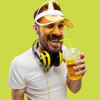Halblanges nahaufnahmeporträt des jungen mannes im hemd. männliches model mit kopfhörern und getränk. die menschlichen gefühle, gesichtsausdruck, sommer, wochenendkonzept. lächeln und trinken.