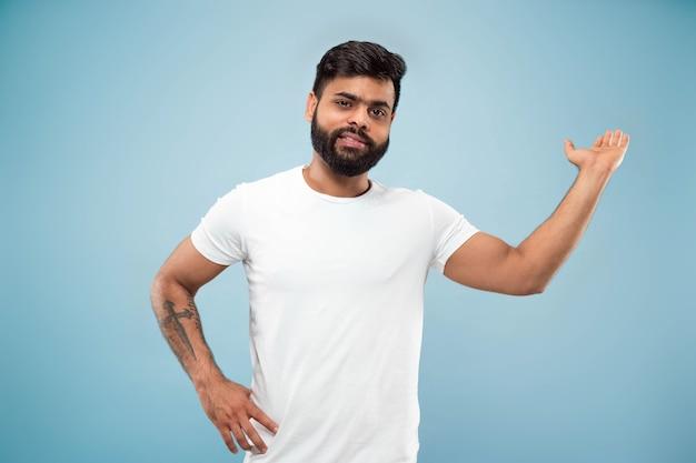 Halblanges nahaufnahmeporträt des jungen mannes im weißen hemd auf blau
