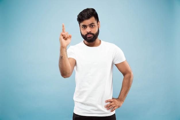 Halblanges nahaufnahmeporträt des jungen mannes im weißen hemd auf blauer wand