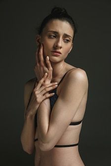 Halblanges porträt der jungen traurigen frau in unterwäsche auf dunkler studiowand
