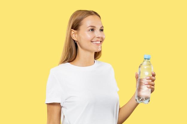 Halblanges porträt der kaukasischen jungen frau auf gelbem studiohintergrund. schönes weibliches modell im weißen hemd. konzept menschlicher emotionen, gesichtsausdruck. trinkwasser aus der flasche.