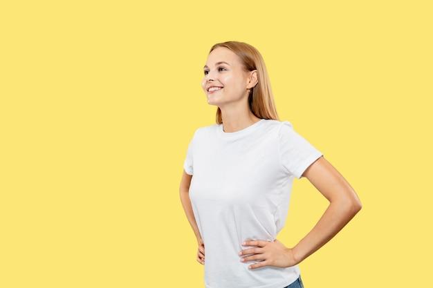 Halblanges porträt der kaukasischen jungen frau auf gelbem studiohintergrund. schönes weibliches modell im weißen hemd