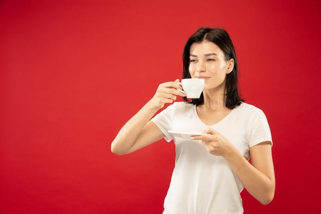 Halblanges porträt der kaukasischen jungen frau auf rotem studiohintergrund. schönes weibliches modell im weißen hemd. konzept menschlicher emotionen, gesichtsausdruck. trinkt gerne kaffee oder tee, sieht ruhig aus.