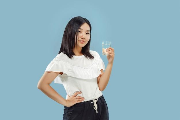 Halblanges porträt der koreanischen jungen frau auf blauem hintergrund