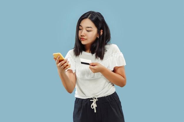 Halblanges porträt der koreanischen jungen frau auf blauem raum. weibliches modell mit ihrem smartphone zum bezahlen von rechnungen oder zum online-kauf.