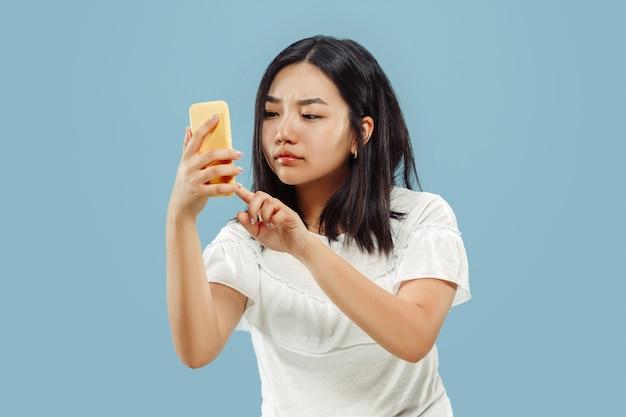 Halblanges porträt der koreanischen jungen frau. weibliches modell im weißen hemd. mit ihrem smartphone. konzept menschlicher emotionen, gesichtsausdruck. vorderansicht.