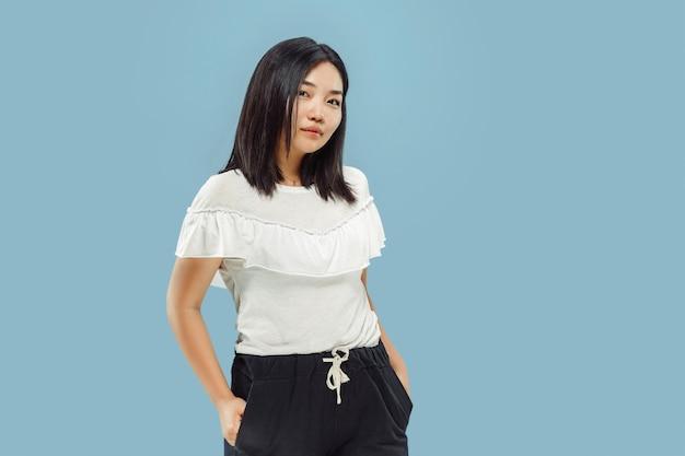 Halblanges porträt der koreanischen jungen frau. weibliches modell im weißen hemd. stehend und lächelnd. konzept menschlicher emotionen, gesichtsausdruck. vorderansicht.