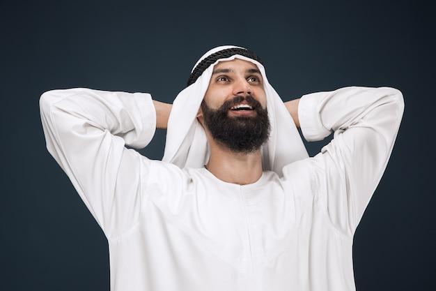 Halblanges porträt des arabischen saudischen geschäftsmannes auf dunkelblau