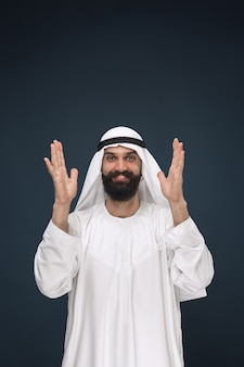 Halblanges porträt des arabischen saudischen geschäftsmannes auf dunkelblauem raum. junges männliches modell stehend und lächelnd